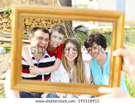 Happy family in a frame.  Happy family in a frame on the background of the construction of their new home. - stock photo