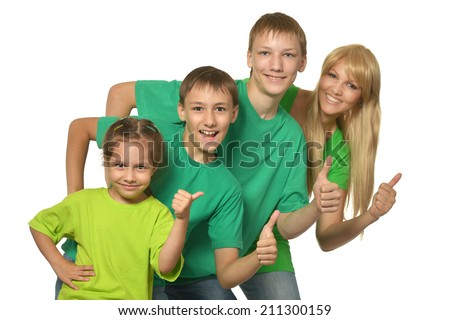 Happy family in a green clothes showing OK sign in studio