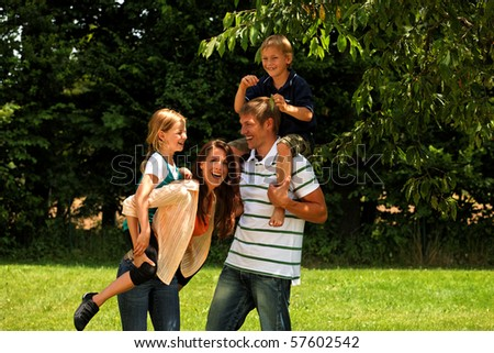 happy family in a park - piggypack - stock photo