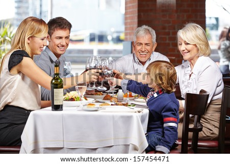 Happy family in a restaurant clinking their glasses of wine and water - stock photo