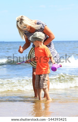 happy family in action mother and son playing on beach - stock photo