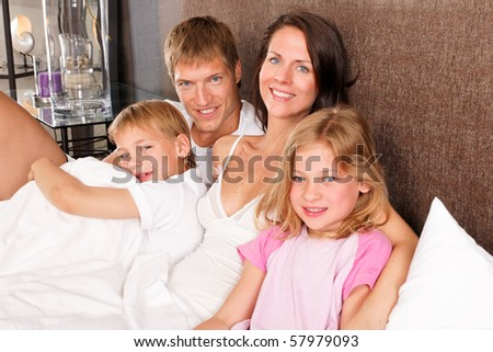 happy family in bed - good morning - stock photo