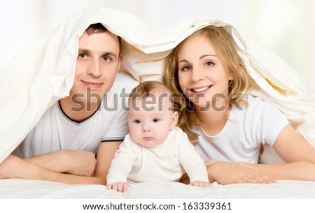 happy family in bed under a blanket. mother, father, baby - stock photo
