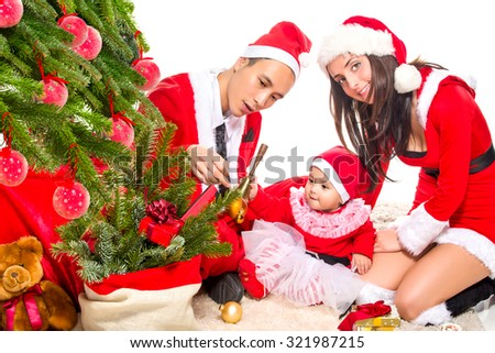 Happy family in Christmas eve at home sitting near decorated fir tree  - stock photo
