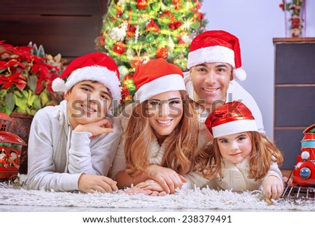 Happy family in Christmas eve, cheerful parents with two cute kids lying down on the floor near beautiful decorated Xmas tree - stock photo