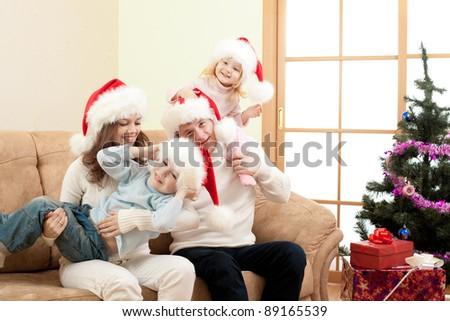 happy family in Christmas Santa's hats on sofa in living room - stock photo