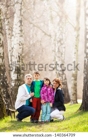 Happy family in countryside forest; mother, father, son and daughter. - stock photo