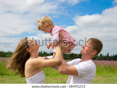 Happy family in field or meadow - stock photo