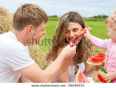 Happy family in haystack feeding mother with watermelon - stock photo