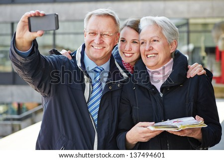 Happy family in holiday taking self portrait with their smartphone - stock photo