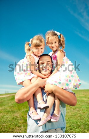 Happy family in outdoor park  at sunny day. Dad and two daughters in the green garden.  Group of people on green grass. - stock photo