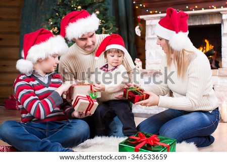 Happy family in Santa hats with gifts sitting at Christmas tree near fireplace - stock photo