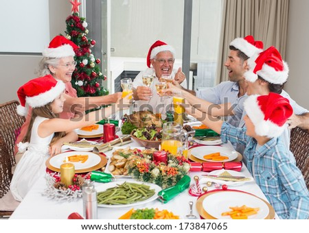 Happy family in santas hats toasting wine glasses at dining table in the house - stock photo