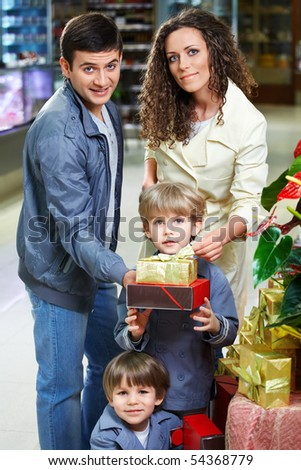 Happy family in shop with boxes of gifts - stock photo
