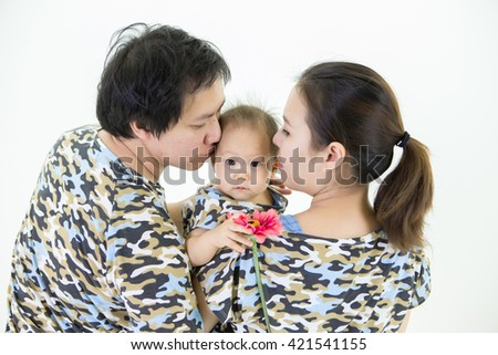 Happy family in similar dress, dad and mom kiss on their little daughter - stock photo