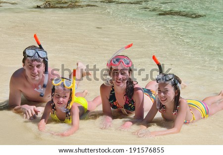 Happy family in snorkels on tropical beach having fun on sea vacation