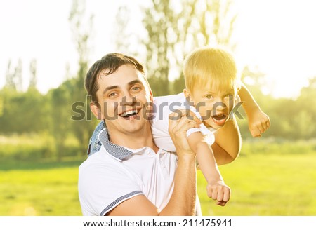 happy family in summer nature. Dad and son hugging, playing and laughing - stock photo