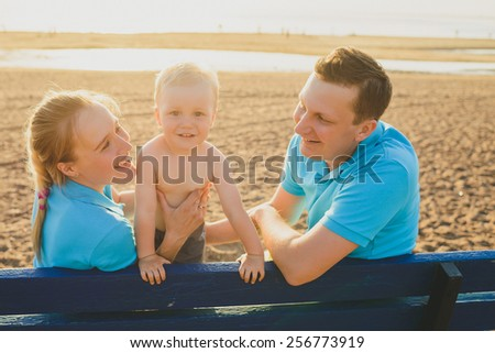 happy family in summer on a walk to the sea. sunset - stock photo