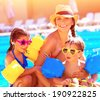 Happy family in summer vacation, young mother with two cute kids having fun near swimming pool on beach resort, love and friendship concept - stock photo