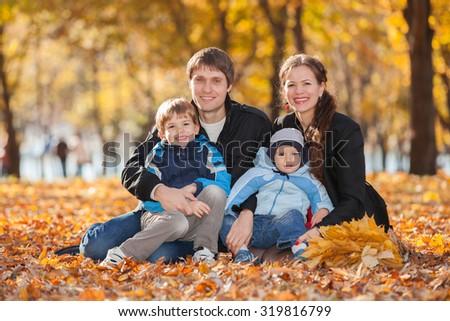 Happy family in the autumn park - stock photo