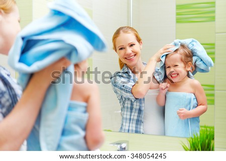 happy family in the bathroom. mother of a child daughter with a towel dry hair - stock photo