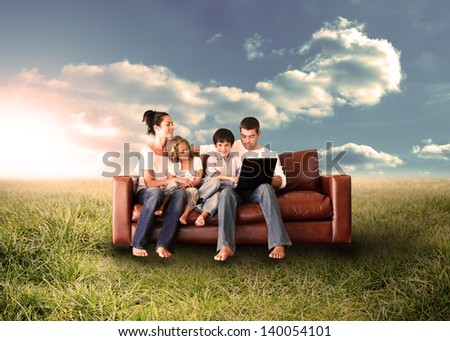 Happy family in the couch using the laptop in a sunny field in the countryside - stock photo