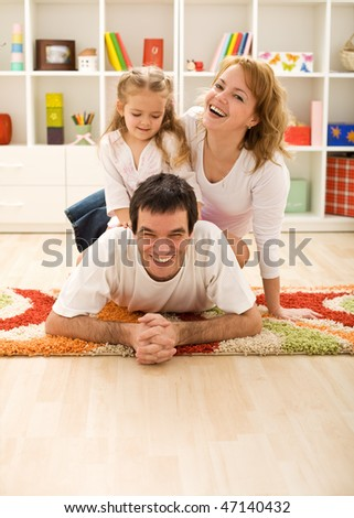 Happy family in the kids room laying on the floor - stock photo