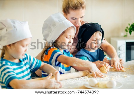 happy family in the kitchen. mother and children preparing the dough, bake cookies