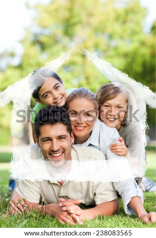 Happy family in the park against house outline in clouds