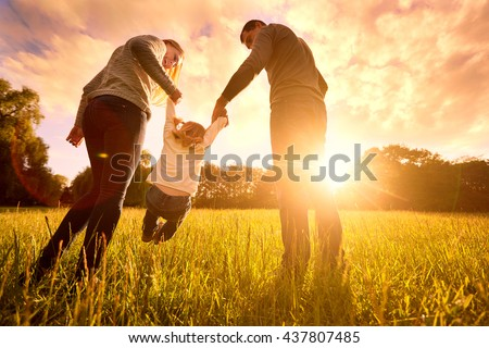 Happy family in the park evening light. The lights of a sun. Mom, dad and baby happy walk at sunset. The concept of a happy family.Parents hold the baby's hands. - stock photo