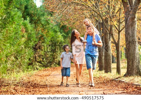 Happy family in the park for a walk in the summer, in the fall. Mother, father and two children walking on nature. Parents and children smile, laugh, play in the afternoon.