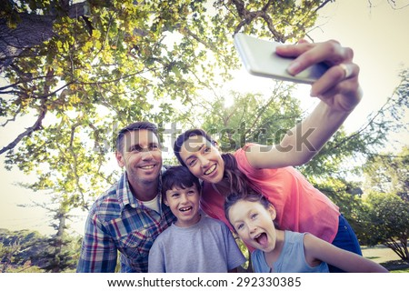 Happy family in the park taking selfie on a sunny day - stock photo