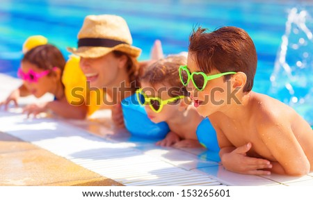Happy family in the pool, having fun in the water, mother with three kids enjoying aquapark, beach resort, summer holidays, pleasure concept  - stock photo