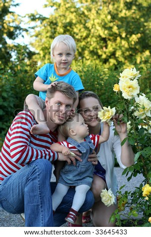 Happy family in the rose garden - stock photo