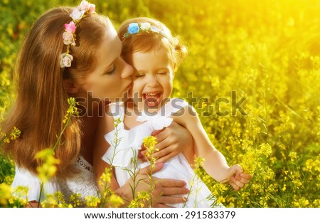 happy family in the summer meadow, mother kissing little daughter girl child with yellow flowers - stock photo
