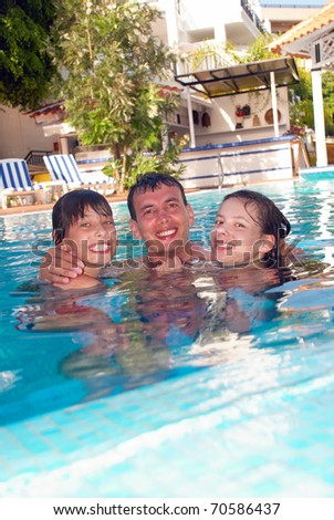 Happy family in the swimming pool of luxury hotel - stock photo
