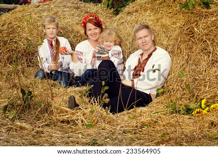 Happy family in the Ukrainian national clothes near a haystack. Father, mother, son and daughter have a rest in the summer in the countryside - stock photo
