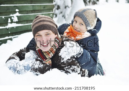 Happy family in the winter. Young father playing with son in the snow. It's snowing. - stock photo