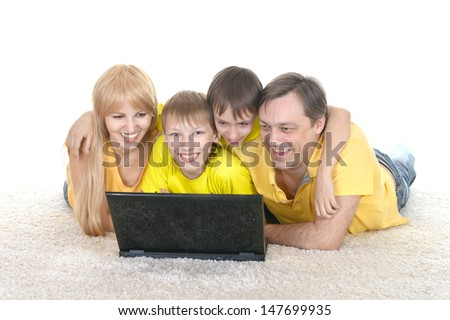 happy family in the yellow shirt resting at a laptop