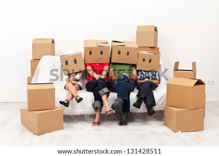 Happy family in their new home having fun together sitting on the sofa - stock photo