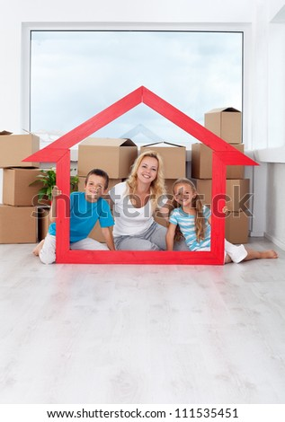 Happy family in their new home laughing by a large house shaped frame - stock photo