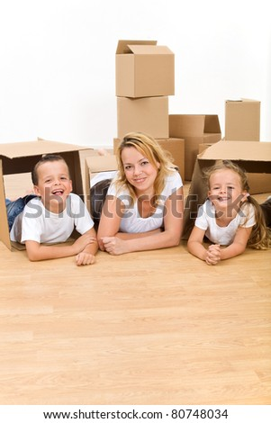 Happy family in their new home laying on the floor with cardboard boxes