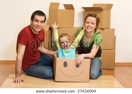 Happy family in their new home sitting on the floor with cardboard boxes around - stock photo