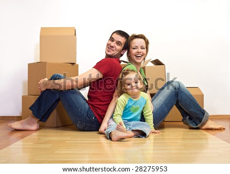 Happy family in their new home with cardboard boxes - moving concept - stock photo