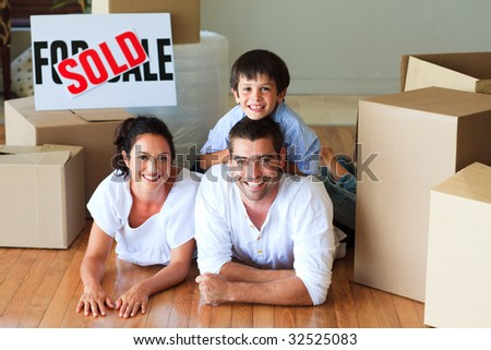 Happy family in their new house lying on floor with boxes
