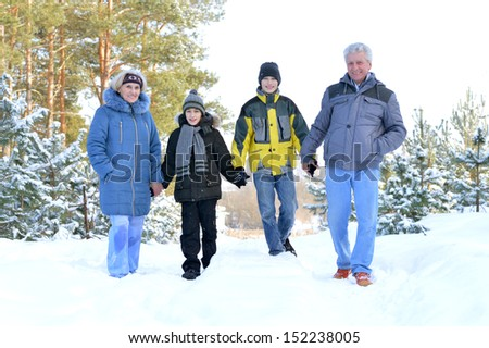 Happy family in warm clothing in winter outdoors - stock photo