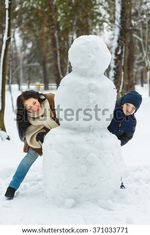 Happy family in warm clothing. Smiling mother and son standing next to a snowman outdoor. The concept of winter activities - stock photo