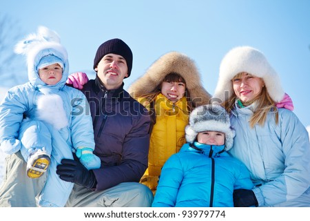 Happy family in warm winter clothes against blue  sky