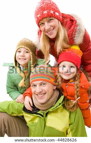 Happy family in winter clothes looking at camera and smiling - stock photo