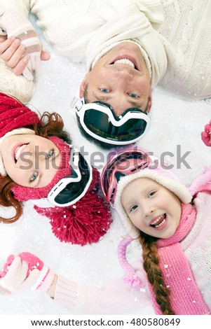 Happy family in winter clothing lying on snow and smiling at camera